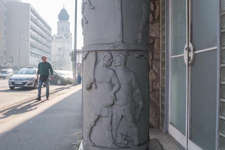 Ez a két óriás oylan szeretettel néz egymásra, hogy észre sem veszik a lábuknál János vitézt. A háttérben a kecskeméti zsinagóga látszik.