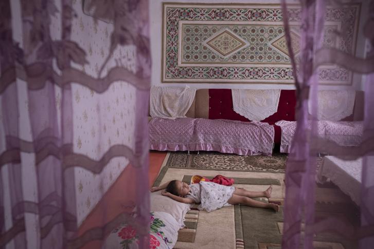 Egy 5 éves kislány alszik, akinek az édesanyját 18 hónapig fogva tartották egy hszincsiangi táborban.