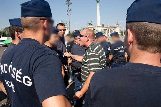 Egy jobboldali tüntető ordít a rendőrökkel miután meg akarta támadni Dániel Péter ügyvédet baloldali aktivistát.