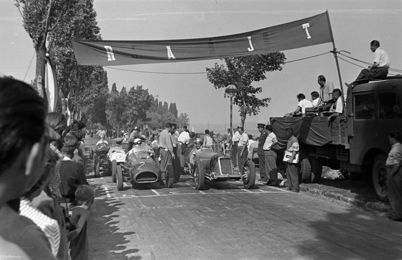 """Az """"Építők 1957. IX. 8-i Tihanyi Motorkerékpár és Autóversenye"""" nagydíj autós futamának startja. Balra, az első sorban 2-es rajtszámmal Wimmer András, a III-as Számú Autójavító Nemzeti Vállalat versenyzője és a """"Nagy Hármas"""" (Bugatti-alvázas, BMW motoros versenyautó), jobbra, 4-es rajtszámmal Széles Tibor, a IV-es számú Autójavító NV által benevezett legendás 3015-ös alváz- és motorszámú Maserati 8CM-3000 volánjánál. A második sorban látható Mercedes jelvényes autó Sabján László (VI-os Számú Autójavító NV) két, háború előtti Mercedesből összeépített SJB Specialja. Mögötte, az utolsó sorban 3-as rajtszámmal Kozma Ferenc és Fiat motoros """"Kis Hármas""""-a."""