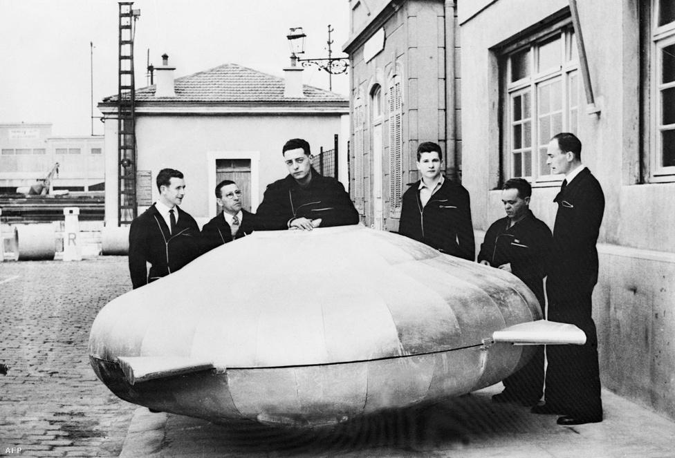 Cousteau és kollégái pózolnak 1957 márciusában a 350 méteres mélységig lemerülni képes SP 350 Denise nevű tengeralattjáró modelljével. A két méter átmérőjű, másfél méter magas Denise-t már elektronikusan szabályzott vízsugarakkal lehetett irányítani, és képes volt a vízben lebegve körbefordulni a függőleges tengelye körül.