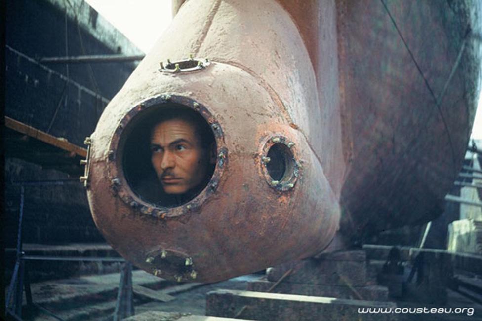 """Cousteau a Calypso speciális megfigyelőállásában: az eredetileg aknakereső hajóként szolgáló járművet a kutató tervei alapján alaposan átalakították, például ez a 3 méterrel a vízszint alá nyúló """"orr"""" is utólag került rá."""