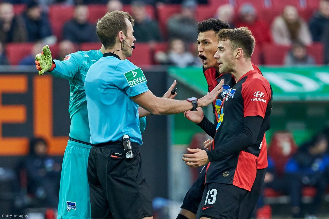 A Hertha játékosai, Davie Selke és Lukas Kluenter vitatkoznak a bíróval az Augsburg elleni mérkőzésen, amin 4 góllal kikaptak 2019. november 24-én