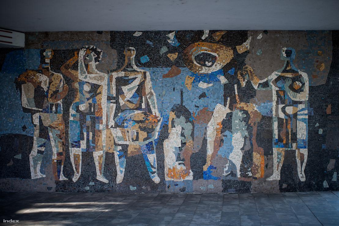 Az árkádok alatt megbújó murálnak nincs neve (hivatalosan Homlokzati mozaiknak hívják), de leginkább A Nap dicsőítéseként emlegetik Túry Mária munkáját