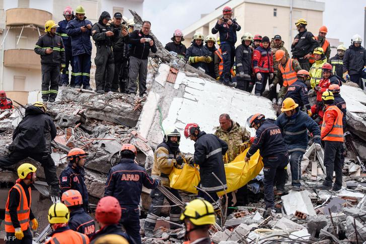 Mentőcsapatok és tűzoltók egy áldozatot emelnek ki a romok alól a nyugat-albániai Durres városában 2019. november 28-án