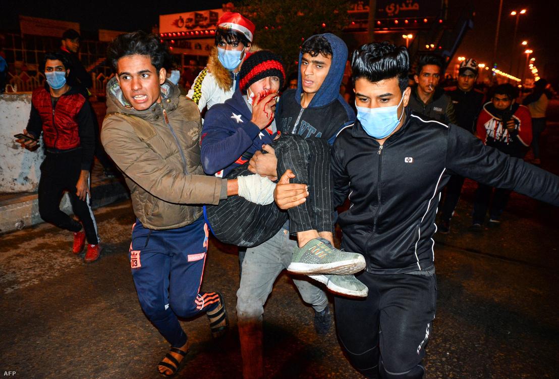 Egy sérültet visznek iraki tüntetők egy kormányellenes demonstráción 2019. november 28-án, Nedzsef városban