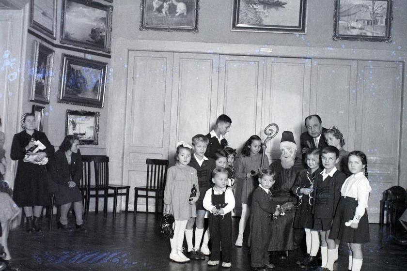 Az óvodákban, iskolákban és bölcsődékben is rendre megjelent minden évben. Ugyan 1946-ban egy igen ijesztő, halottimaszk-szerű álarcot viselő ember foglalt helyet a kicsik között, láthatóan neki is nagyon örültek a gyerekek - bár tény, hogy nem sokan mosolyognak.