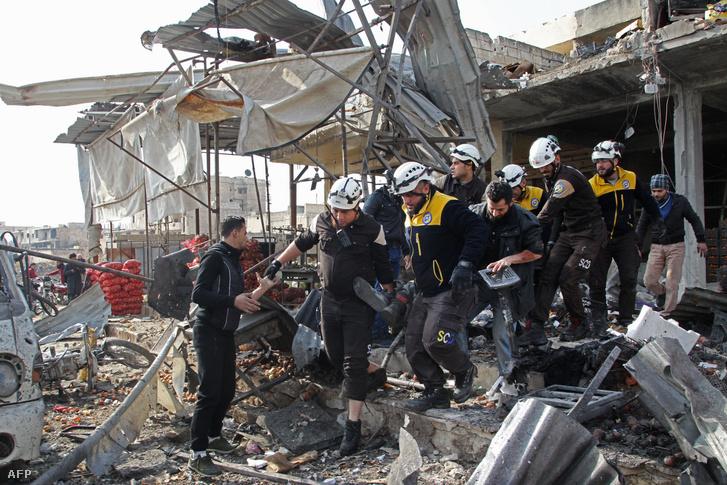 A Szíriai Polgári Védelem tagjai emelnek ki egy áldozatot a romok közöl a szíriai Ildíb tartományban lévő Maarrat-en-Numán piacán 2019. december 2-án
