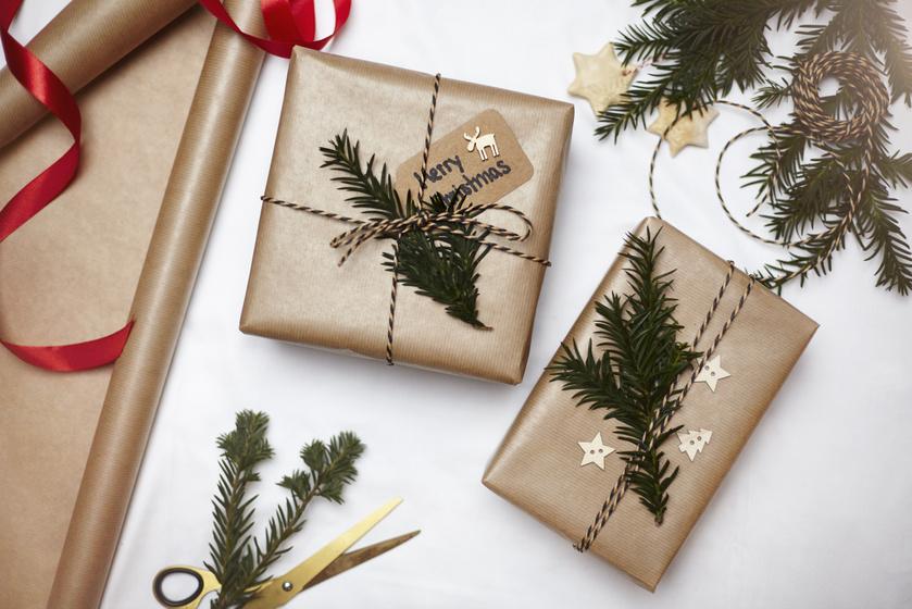 Felejtsd el a műanyag ajándéktáskákat, és alkoss valami igazán egyedit! Ehhez a megoldáshoz egy natúr, barna színű csomagolópapírra, pár zöldellő és illatozó fenyőágra, valamint fából készült dekorelemekre lesz szükséged. A látványt színes madzaggal dobhatod fel.