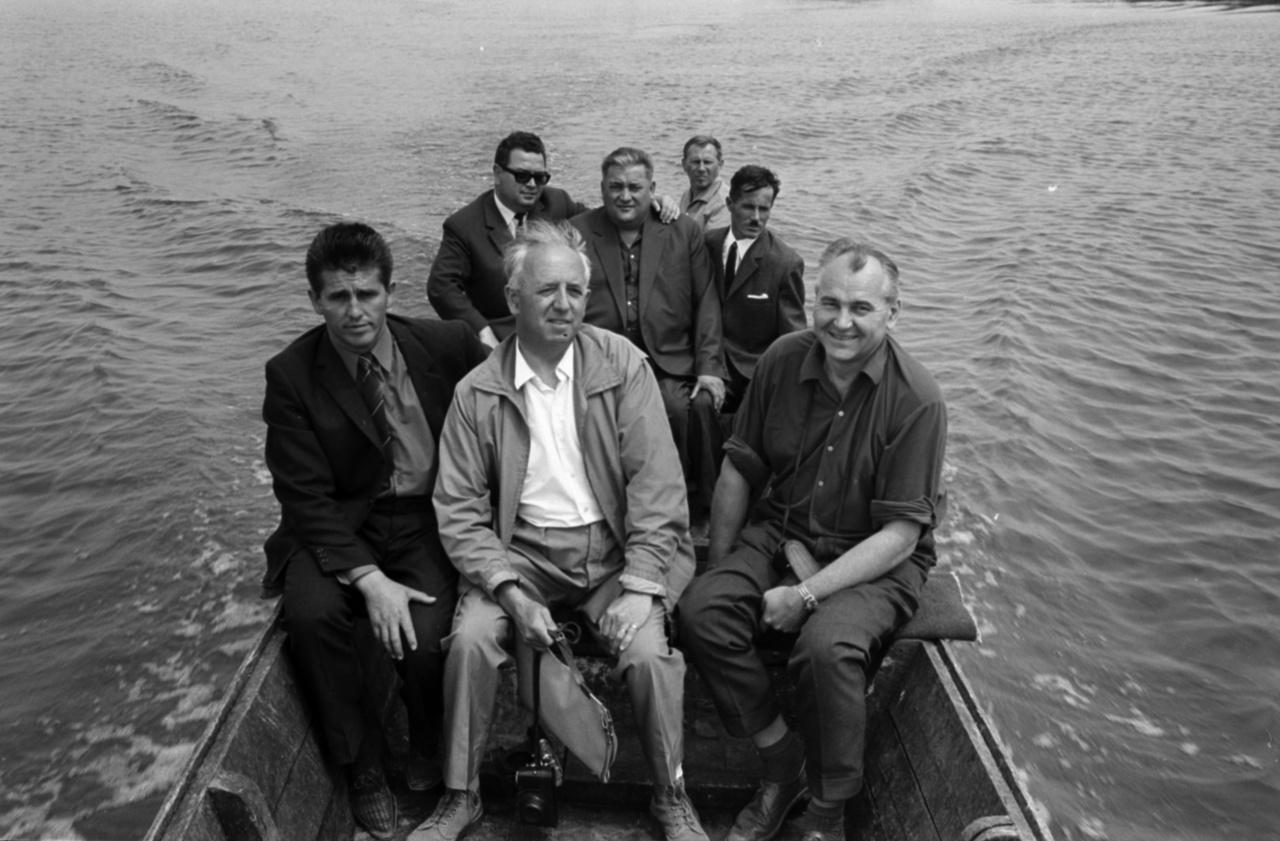 Öltönyös csoportkép a tavon.A minisztériumból lejöttek az elvtársak ellenőrizni a Kutatóintézetet, és az egyik halász megcsónakáztatja őket. Bezzeg erre a csónakra jutott motor, míg a Badacsony alatti halászoknak evezőkkel kellett küszködni.
