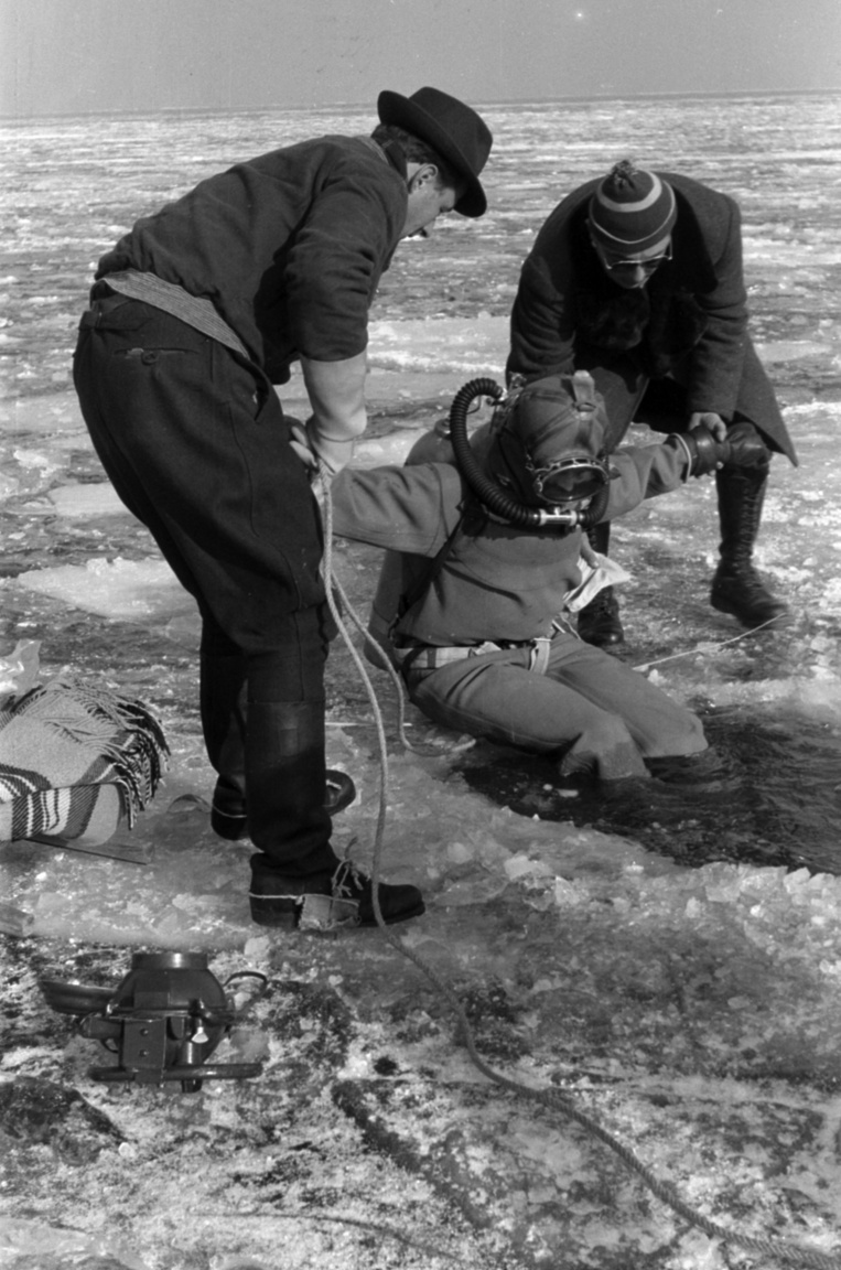 """Jég alatti nehézbúvárkodás a Balatonon, talán halszámlálás, talán ivarérett halak begyűjtése miatt. A magas, kalapos férfi Dr. Felföldy Lajos botanikus és hidrobiológus, a sapkás, napszemüveges Dobos Gyula asszisztens és az intézet hajóvezetője.A tihanyi Magyar Biológiai Intézetet Klebelsberg Kuno alapította 1927-ben. A közoktatási miniszternek nem volt könnyű dolga, a húszas évek nehéz politikai és gazdasági helyzetében többször megkapta a """"Minek egy ekkora gondban lévő országnak egy csiborpatkoló?""""-kérdést."""