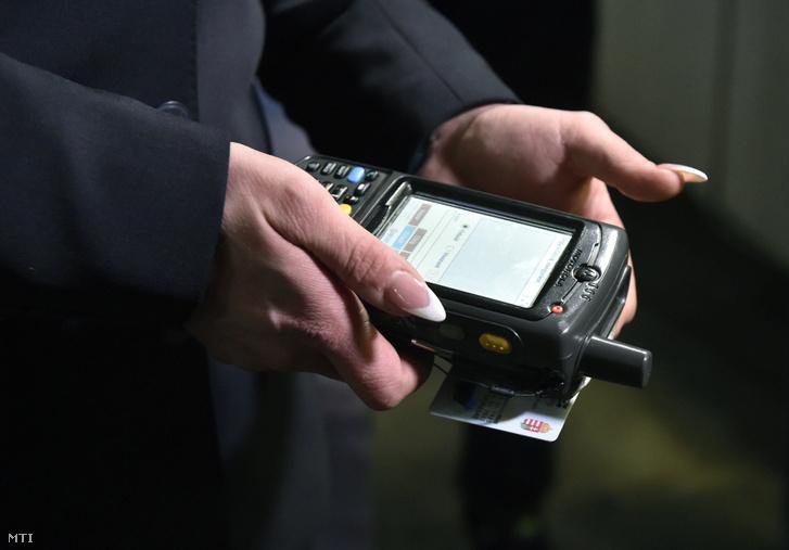MÁV-jegyvizsgáló ellenőrzi egy utas személyi igazolványáról a vasúti bérlet adatait