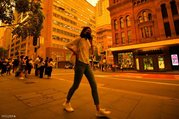 Védőmaszkot viselő gyalogos a Sydney-t beborító bozóttűz füstjében 2019. december 6-án