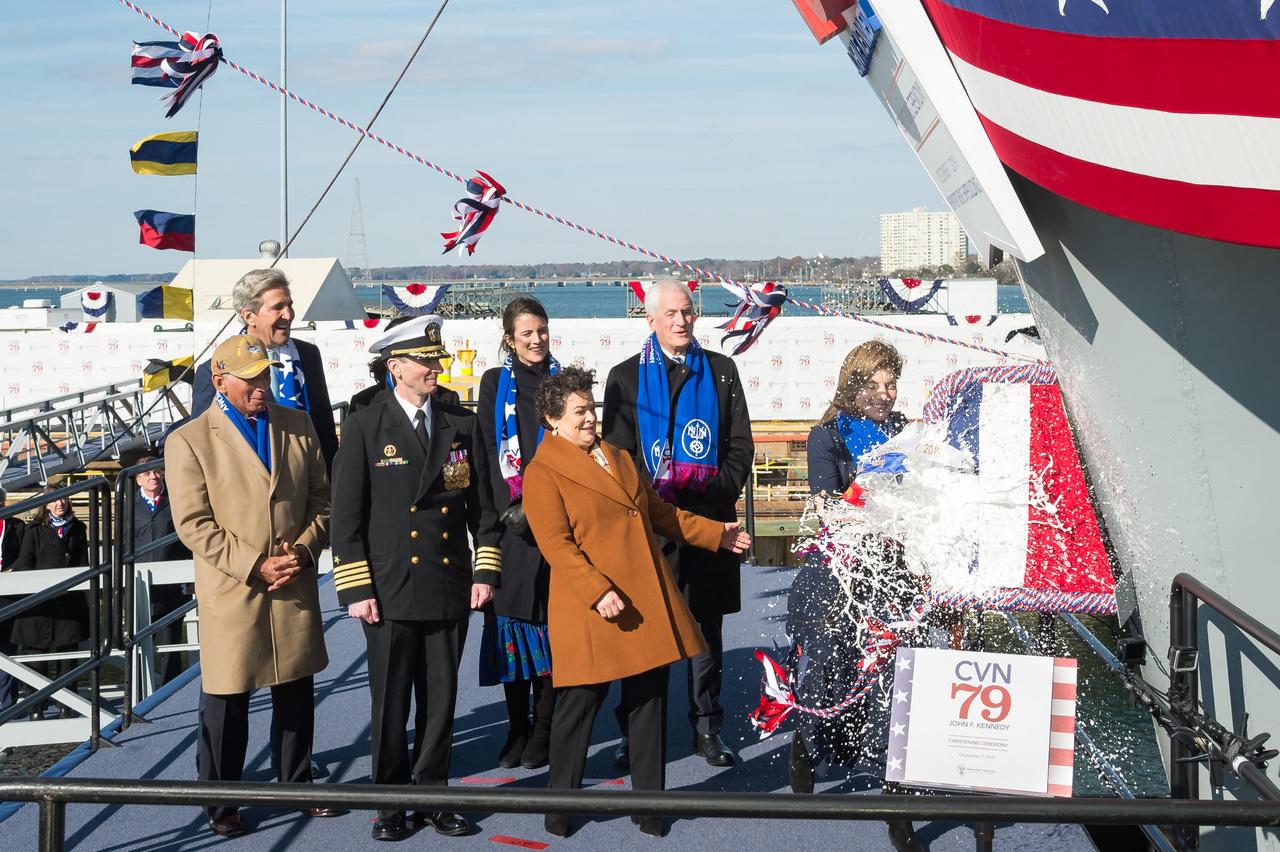 2019. december 7-én ünnepélyes keretek között keresztelte el a hajót Caroline Kennedy, a névadó, John F. Kennedy, néhai amerikai elnök lánya. A fotón illusztris társaság látható: bal szélen Charlie Bolden, a NASA előző igazgatója, mellette John Kerry, az USA korábbi külügyminisztere, Todd Marzano tengernagy, a hajó leendő parancsnoka (egyenruhában), illetve Jennifer Boykin, a Newport News hajógyár elnöke (barna kabátban), mögötte Caroline Kennedy lánya,Tatiana Schlossberg és veje, Edwin Schlossberg.