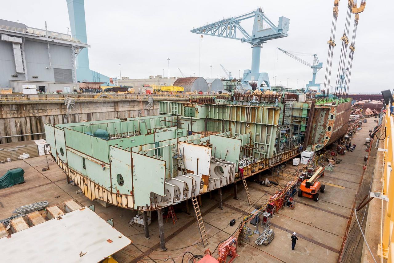 """A hajótest egyik oldalsó elemének helyreillesztése. A több száz tonnás fődarabokat az 1050 tonnás emelőkapacitású """"Big Blue"""" nevű daruval emelik és viszik a szárazdokkban testet öltő hajókhoz."""
