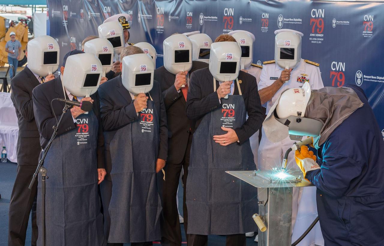 2015. augusztus 22-én ünnepélyesen megkezdődött a USS John F. Kennedy (CVN 79) repülőgép-hordozó építése. A képen Leon Walston, a Newport News Hajóépítő Vállalat dolgozója hegeszti  Caroline Kennedy nevének kezdőbetűit egy acéllapba, a munkást a meghívott magas rangú vendégek hegesztőmaszk mögül figyelik.