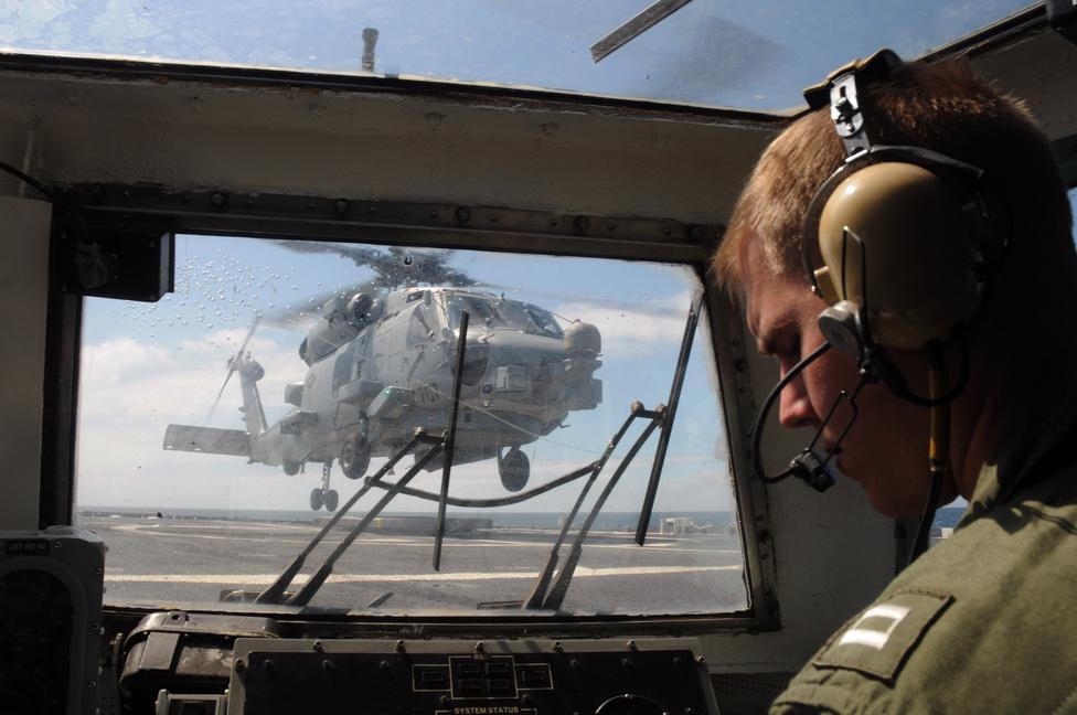 A landolás biztonságáért felel Matthew Pillon hadnagy a Ticonderoga-osztályú USS Normandy rakétacirkálón, itt épp egy MH-60R Magnum 707 helikopter visszatérését felügyeli.