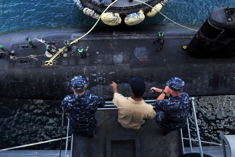 A Los Angeles-osztályú USS Tucson támadó tengeralattjáró kikötését figyelik a USS Emory S. Land tengeralattjáró-támogató hajó fedélzetéről.