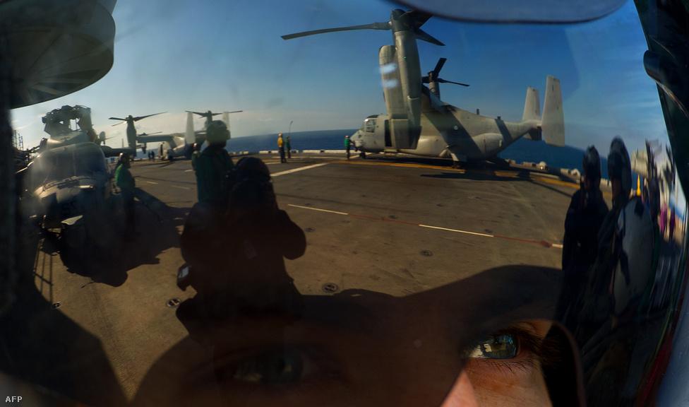 Justin Mears, egy CH-60S helikopter pilótája hajója fedélzetét szemléli, ahol két Bell Boeing V-22 Osprey helyből felszállni képes, forgatható rotorú repülőgép pihen.