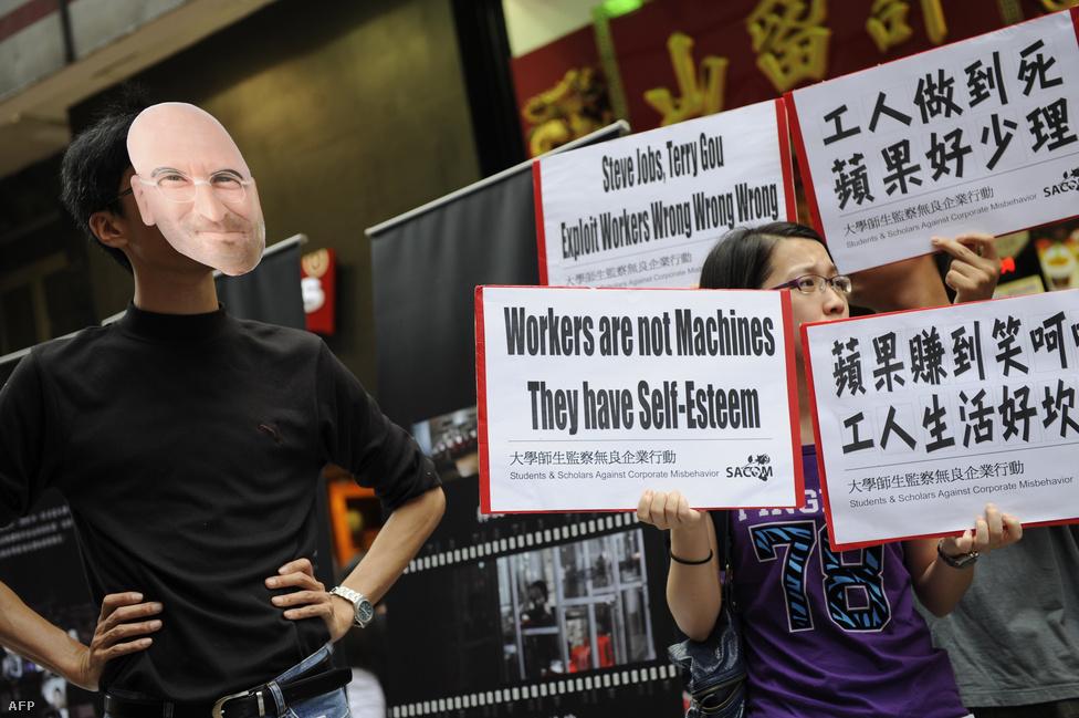 Az Iphone-ok a Foxconn nevű tajvan cég gyáraiban készülnek. A Foxconn dolgozói körében gyakori az öngyilkosság, amit a lelketlen munkakörülmény, a rabszolgasorhoz hasonlító munkakörülmények rovására írnak. A képen egy Hong Kong-i tüntetés résztvevői demonstrálnak az Apple és a Foxconn ellen 2011. május 7-én.