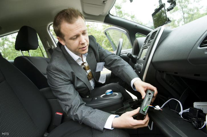 Virág László, a Commsignia informatikai cég technológiai igazgatója mutatja a járművek közötti kommunikációt megvalósító eszközüket az I. Commsignia - BME HIT - autonóm járműtechnológiák workshopján 2016-ban