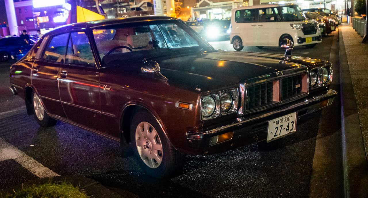 Nissan Laurel a hetvenes évek végéről, ocsmány dísztárcsákkal. Pont ilyen, ráadásul ilyen színű szolgálati autónk volt Japánban három és fél éven át