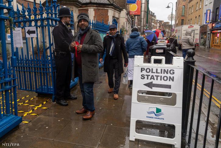 Szavazóhelyiség előtt állnak férfiak London Tower Hamlets nevű keleti negyedében 2019. december 12-én