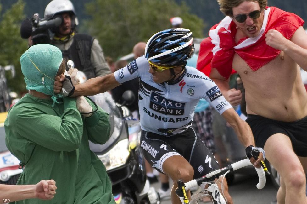 A hegyi szakaszokon örjőngő nézők között teker a mezőny. Alberto Contador 2011-ben az Alp d' Huezen üt meg egy ellenszurkolót, aki a doppingügyére emlékezteti.