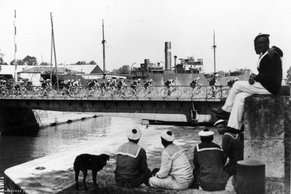 Matrózok nézik az 1925-ös verseny mezőnyét a a roqueforti kikötőben. A Tour ebben az évben szinte végig Franciaország határvonalain haladt, 5430 kilométeren.