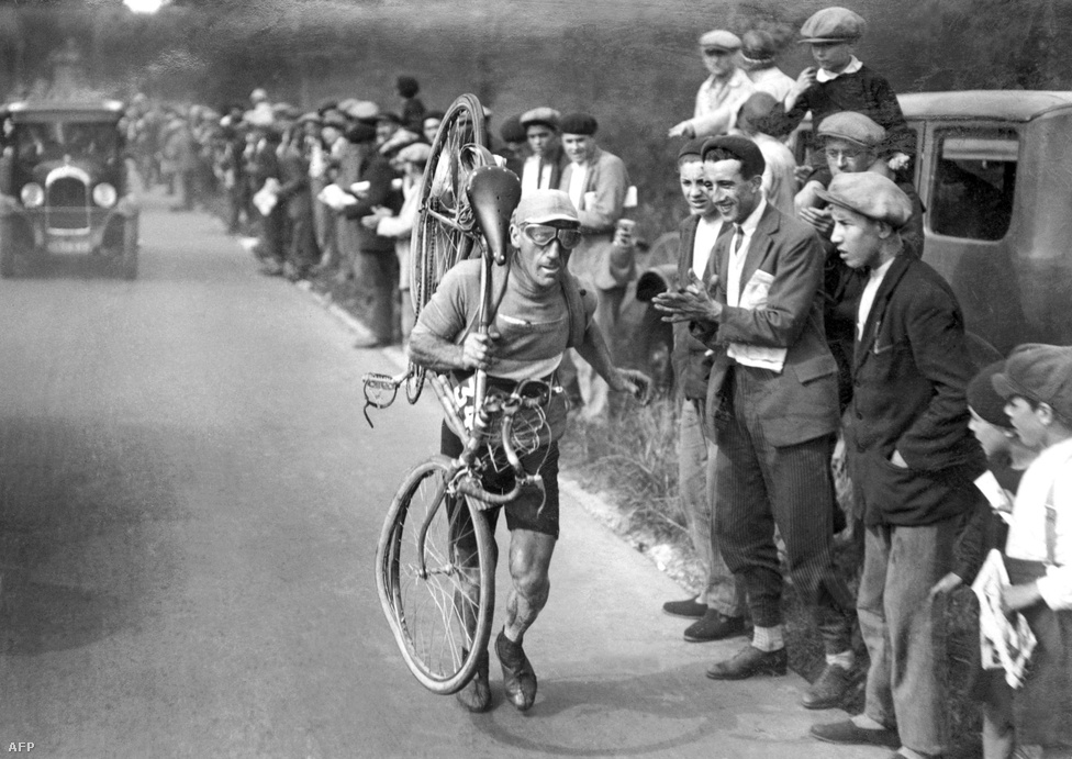 Victor Ponte cipeli a cél felé a kerékpárját az 1930-as versenyen. A verseny hőskorában tilos volt bármiféle segítséget elfogadniuk a versenyzőknek, maguk javították a kerékpárjaikat is.