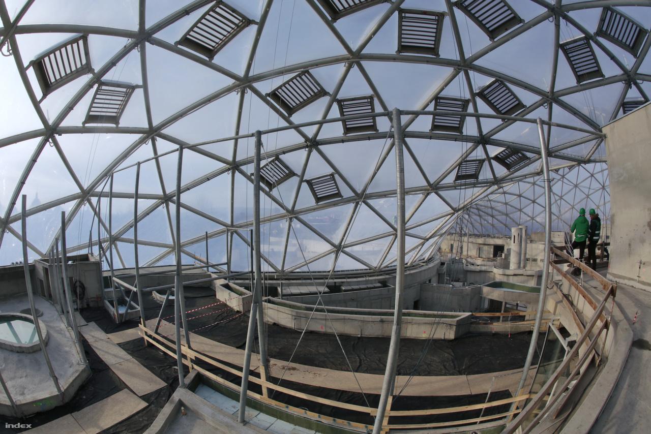 A moduláris tetőszerekezetet alkotó, 964 darab, egyenként 18-20 négyzetméteres háromszög alakú mezőből csak néhányra nem került fel a fóliapárna technológiai okok miatt, hiszen így lehet még az épület egyes részeibe anyagokat bejuttatni. A fotón jól megfigyelhetők a szellőzőablakok.