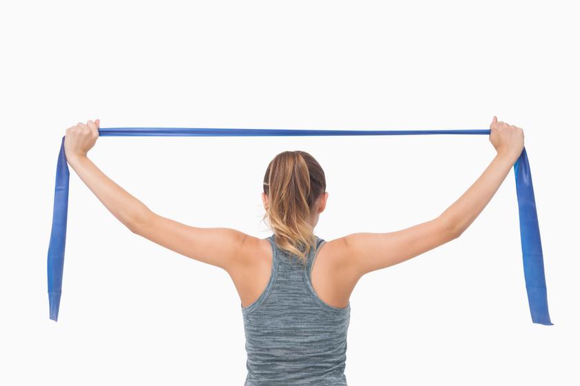 Vállszélességben tartsd a fejed felett a szalagot, majd távolítsd el a két karodat egymástól. Ez a gyakorlat szépen formálja a vállat és a hátat.