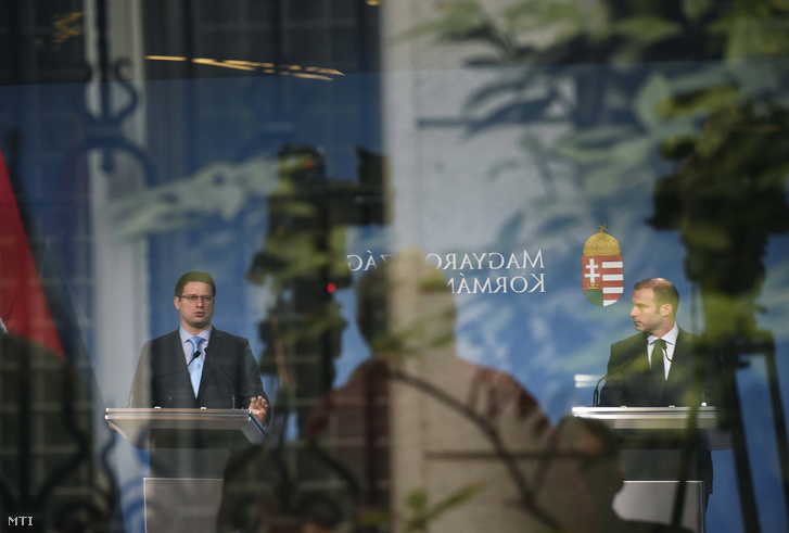 Az üvegfelületen tükröződő képen Gulyás Gergely (balra) és Hollik István kormányszóvivő a mai Kormányinfó sajtótájékoztatón.