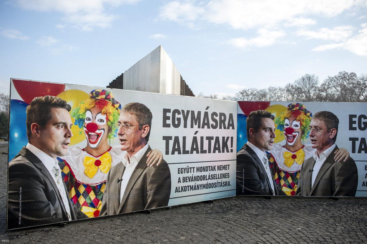 """A Civil Összefogás Fórum (CÖF) újabb plakátja a budapesti Ötvenhatosok terén 2016. december 7-én. A kép Vona Gábor Jobbik-elnököt és Gyurcsány Ferenc DK-elnököt öleli át a korábbi plakátkampányból ismert bohóc, a felirat pedig azt hirdeti: """"Egymásra találtak! Együtt mondtak nemet a bevándorlásellenes alkotmánymódosításra""""."""
