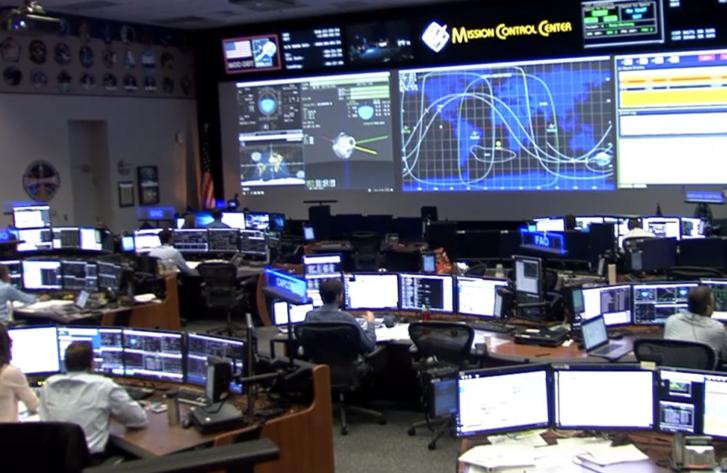 A NASA houstoni küldetésirányító központja, a képernyőkön az űrhajó mozgását mutató valós idejű animáció és világtérkép