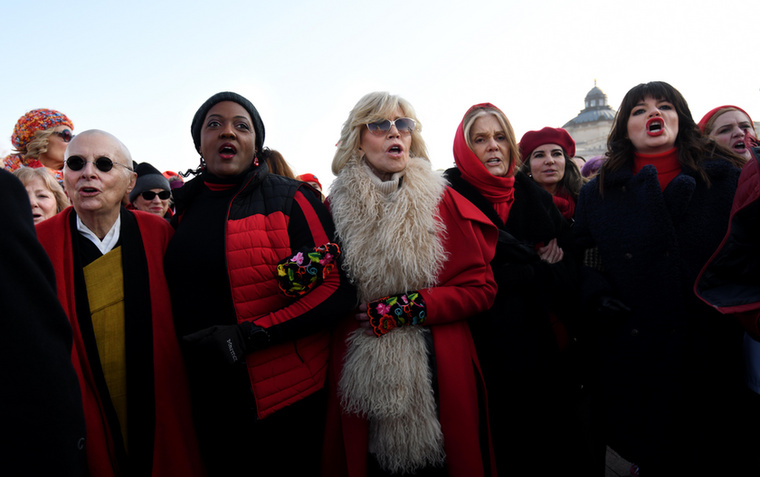 Hiába karolnak egymásba testvériesen, és öltöztek pirosba, a karácsony színébe, a képen látható emberek (közöttük Jane Fonda) nem karácsonyi dalokat énekelnek