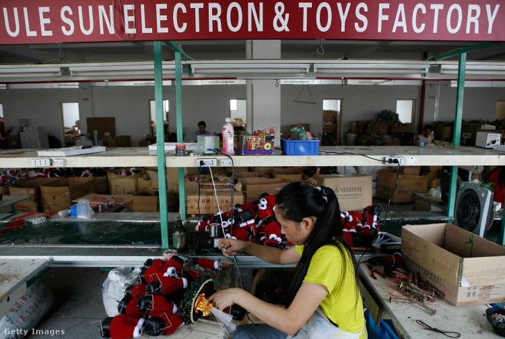 Mikulás figurát készít egy munkás egy kínai játékgyárban