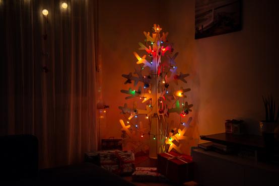 """""""A gyerekek első reakciója az volt: Jé, játékfa! De jó! Etsy-n találtunk rá erre a fára. Az elemei fahulladékból készültek, és egy kicsit emlékeztet az általános iskolai technikaórák alapanyagaira, de egész jól megállja a helyét karácsonyfaként (170cm magas és 80 széles). Az ajándékokat sem rakjuk eldobható csomagolóba, hanem minden évben belehúzzuk őket ugyanabba az ágyneműhuzatból átalakított textilbe."""" (Kollégánk Hernádi Levi)"""