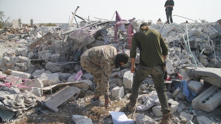 Házak romjai között emberek az északnyugat-szíriai Idlíb tartományban fekvő Barisa falu közelében