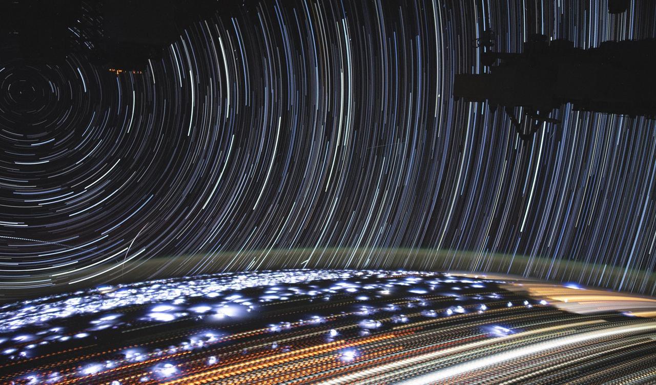 Hosszú expozíciós idővel készült felvétel a csillagok mozgásáról, és a Föld fényeiről