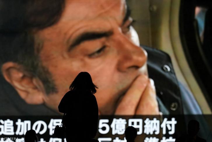 A Japánban pénzügyi visszaélésekkel vádolt Carlos Ghosnról a Nissan járműgyártó cég leváltott elnökéről szóló híradást néznek emberek egy óriási kivetítőn Tokióban