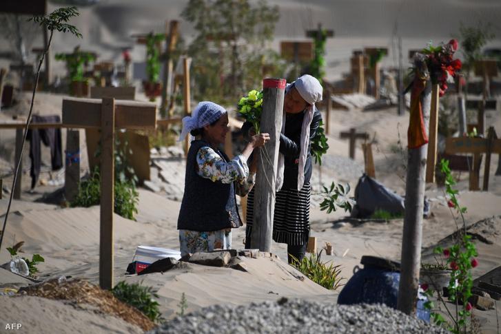 Két nő díszít egy sírt egy ujgur temetőben Hotan külvárosában, Kína északnyugati részén, Hszincsiang tartományban 2019 májusában.