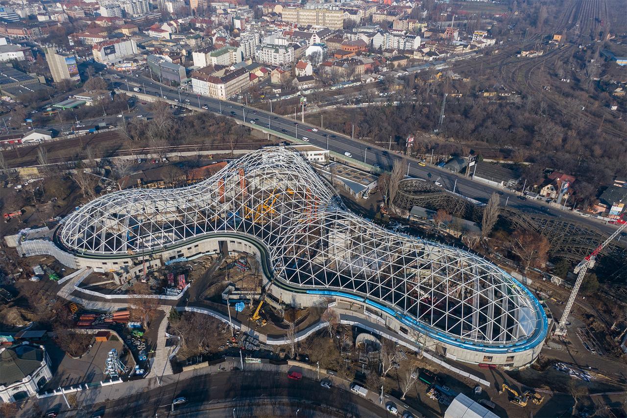 2018. december 14-i fotón a biodóm állapota, amikor még csak a tetőszerkezet volt kész. Az már ekkor látszott, hogy hatalmas épületről van szó, ami jókora területet elfoglal a Városliget sarkában, a XIV. kerület Kacsóh Pongrác úti felüljáró, az Állatkerti körút és a Budapest–Cegléd–Szolnok-vasútvonal által körülhatárolt részén.