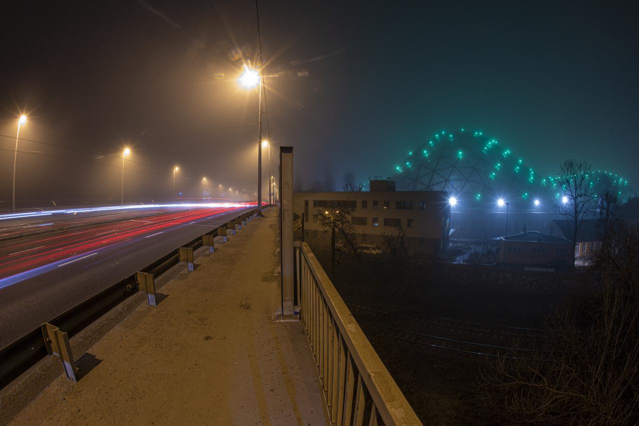 A kivilágított biodóm esti ködben, a Róbert Károly körúti felüljáróról nézve.