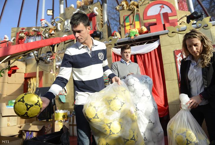 Balogh Gábor, a Magyar Diáksport Szövetség (MDSZ) elnöke Gyurta Dániel és Szász Kitti közreműködésével labdákat pakol a Mikulásgyárban 2014. december 21-én. Az MDSZ szervezésében sportolók ezer darab labdát adtak át a Mikulásgyárnak.