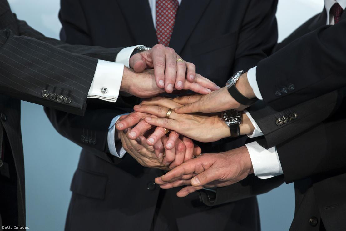 A Renault, a Nissan és a Mitsubishi vezetői kezet ráznak egy sajtótájékoztatón, ahol bejelentették a három cég együttműködését 2019. március 12-én.