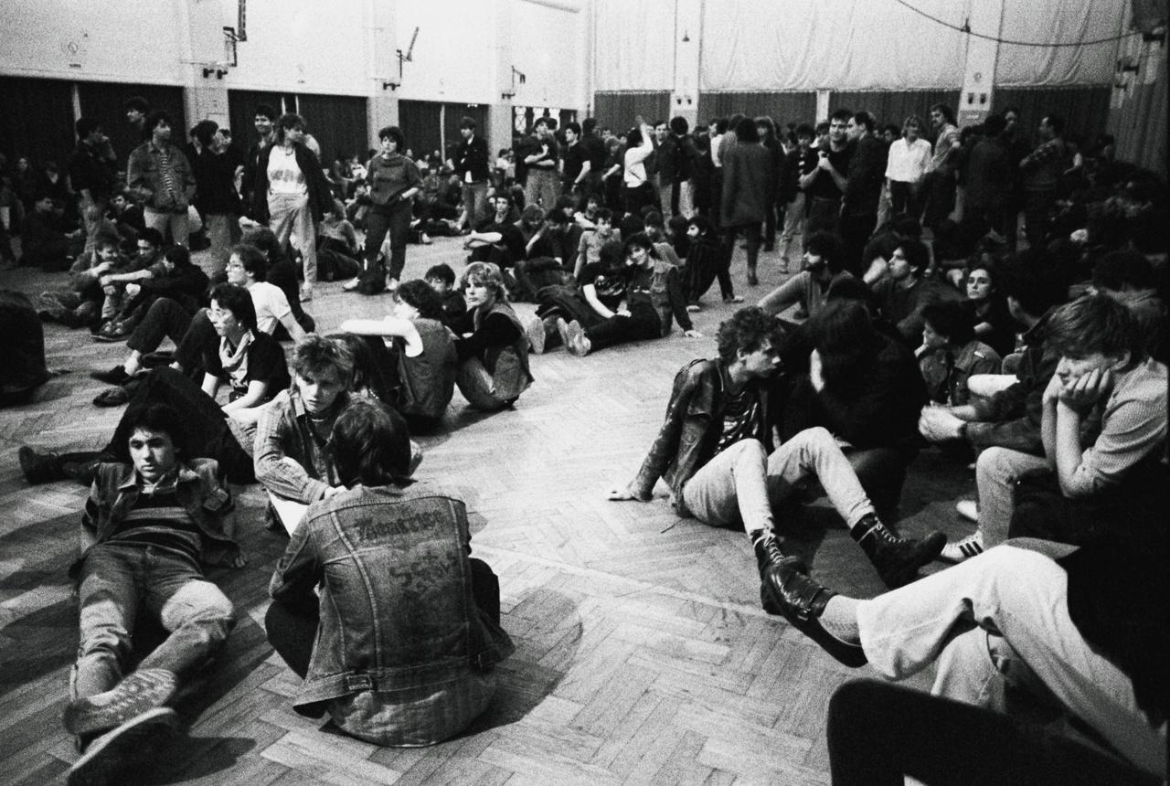 Földön ülő ricsések, illettve egy Beatrice és Sex Pistols-feliratokkal ellátott farmerkabát az előtérben. (Ganz-Mávag Művelődési Központ)