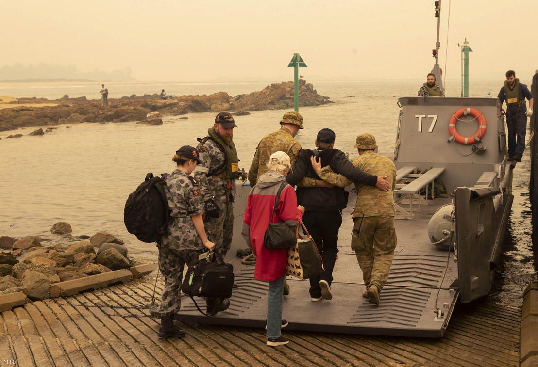 Az ausztrál védelmi minisztérium által közreadott felvétel bozóttűz miatt otthonukat elhagyni kényszerült emberekről akiket katonai vízi járművel visznek az ausztrál haditengerészet Choules nevű hajójára Mallacoota városból 2020. január 3-án.