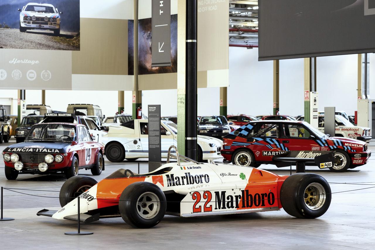 Andrea de Cesaris 1982-es Alfa Romeo Forma-1-es kocsija áll középen, a bejárattal szemben. Mögötte már felsejlik a talán legizgalmasabb rész, a Lancia raliautók csoportja.