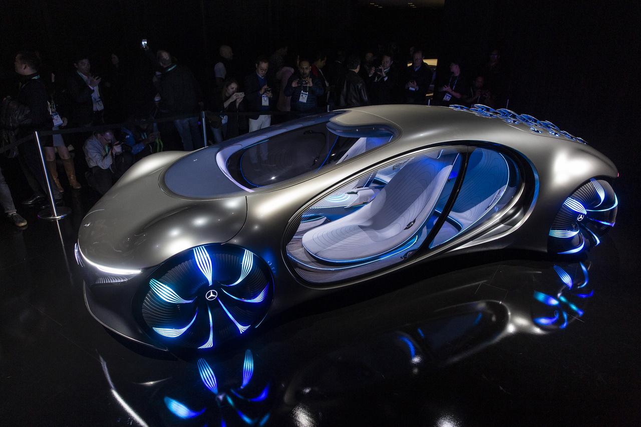 """A legnagyobbat idén a Mercedes-Benz gurította, ami a koncepcióautókat illeti. Nem igazán világos, hogy a marketingen kívül még milyen megfontolásból álltak össze James Cameron filmrendezővel, de a lényeg, hogy az Avatar című film ihletésére építettek egy olyan autót, amitől mindenkinek leesik az álla. A Vision AVTR (Avatar és Advanced Vehicle Transformation egyben) csupa ív és domborulat, csupa fény és árnyék, olyan mint valami organikusan termett luxusgépkocsi topográfiai topográfiai térképe. Már a kerekei lenyűgözőek (egymástól függetlenül mozoghatnak, emiatt az autó képes 30 fokban oldalazva is gurulni), de gyakorlatilag minden egyes részletén hosszan el lehet időzni, a műszerfaltól (amin természetesen nincsenek műszerek, egyetlen íves kijelző az egész) kezdve, az üléseken (igazi kagylóhéjak) át a hátán lévő szellőzőkig (33 bionikus szárnyacska, amik akár kommunikációra is alkalmasak). A Mercedes azt mondja, hogy az elektromos négykerék-meghajtású, 350 kW-os motorral felszerelt Vision AVTR karbonsemleges, újrahasznosítható, környezetbarát anyagokból készült, de még a grafénalapú akkumulátora is komposztálható. Kormánykerék és hasonló haszontalanságok nincsenek benne, a sofőr a középső konzolon lévő érintős kontrollerrel irányítja az autót, a szerkezet érzékeli a vezető szívverését, lélegzetét, így tudja beazonosítani az autó tulajdonosát is. Az autó AI-ja figyeli az utasok alapvető életjeleit is, és azokhoz igazítja az utastér atmoszféráját, az utasok pedig ha fölemelik tenyerüket, az abba vetített kezelőfelületen különféle autóba épített funkciókat tudnak elérni. Az persze teljesen nyilvánvaló, hogy az AVTR sosem lesz sorozatgyártott autó, de a belezsúfolt forradalmi technológiák mindegyike megjelenhet idővel a jövendő autókban. Ha ezek közül egyet kellene kiemelni, akkor az akkumulátor hangik a legígéretesebbnek: a Mercedes szerint az autó energiatárolója """"grafénalapú szerves sejtkémiai"""" elven működik (jelentsen ez bármit is), és semmiféle ritka, mérgező vagy d"""